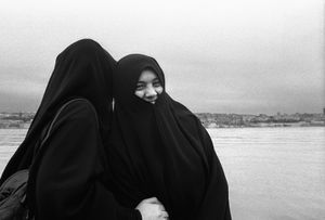 Two women, dressed in Chadors, laugh as they pose for a photo on the shore of the Golden Horn.