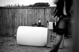 Dallas, Texas, 2010. Tables, rolls of foam and giant barrels provide a makeshift obstacle course against the backdrop of Ralph's dog chewed fence. Ralph's guests waste no time in talking shop; rifle modifications, pistols, and ammo, as they holster weapons. © Spike Johnson