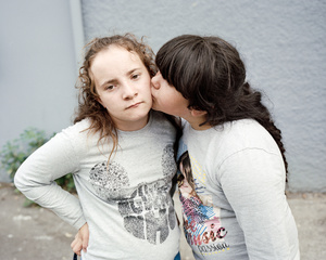 Ilona, 12 years old,  and her sister Maddelena, 11 years old, during a tender moment, in front of the building ( Unit 26) where they live in the Cité Gély, a poor neighbourhood of Montpellier.