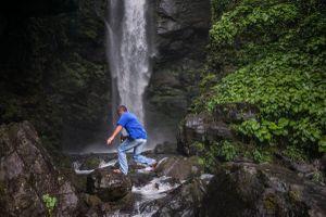 Georgia, Tkvarcheli, AbkhaziaA man jumps across rocks below a waterfall near the former mining town of Tkvarcheli.© Petrut Calinescu