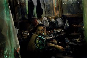 A weary-looking shoe repairman sits in his shop in the neighborhood of El Hussein in Cairo.