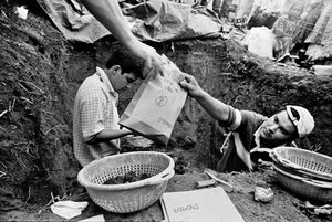 Danny Guzman hands a bag containing ribs of an exhumed body out of a grave. The grave site is treated as a crime scene, and all bones, clothing, everything is meticulously catalogued and recorded as it is removed. © Victor Blue, 2004