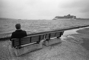 A man, sitting on a bench, watches a cruise liner leaving the Port of Istanbul (Istanbul Limani).