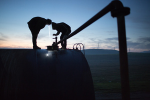 Jamal, 17, and Azdar, 16, watch as fuel oil is pumped into a storage drum at dawn.