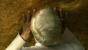 GOLDEN BOULDER, PRAYING <BR>A worshipper kisses the golden boulder at the peak of Mount Kyaikhtyo in Eastern Burma (Myanmar). © Peter Friedman and © Roger Manley