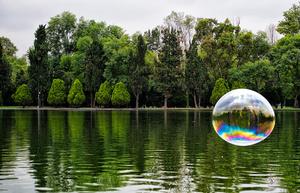 Man walking dog inside a bubble.  Chapultepec Park, Mexico City.