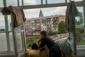 Stepanakert, Nagorno Karabach. A young man, with a cat, looks out of the window of his mother's apartment in Shusha during his last summer holiday before joining the Military School in Yerevan. The Nagorno-Karabakh Republic (NKR) is a de facto independent republic which is not recognized internationally.© Petrut Calinescu