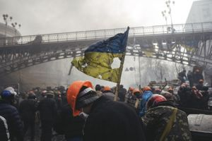 Сlashes between riot police and protesters during the attempting to block Verhovna Rada. A man with tattered Ukrainian flag on Institutska street. In 20 minutes snipers opened fire. Kiev, Feb. 20, 2014