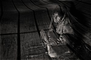 Sorifa Khatun (30) rocks one of her seven children to sleep. Her husband, Kased Mali, was killed by a tiger some six months ago. Gabura, Satkhira. © Munem Wasif/VU'