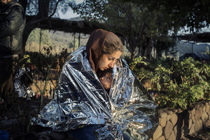 A mother and child wrapped in an emergency blanket after disembarking on the beach of Kayia, on the north of the Greek island of Lesvos, Oct. 18, 2015 - Crossings Exhibition