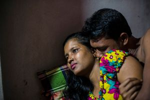 """""""Meghla, 23, with a customer in the Kandapara brothel in Tangail. She started working for a garment factory when she was 12 years old. There she met a man who promised her a better job with more money and he sold her into a brothel"""". From the Series """"The Longing of Others"""". The Kandapara brothel in the district of Tangail is the oldest and one of the largest in Bangladesh - it has existed for some"""