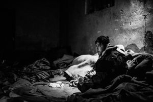 Stranded refugee inside derelict warehouse where is cold, so people have to use blanket to warm themselves, Belgrade, Serbia.