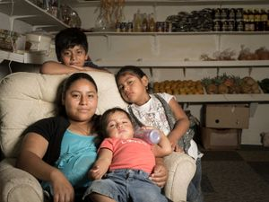 Herminia Hernandez-Bautista is shown with her three children in the fruit and vegetable stand she operates in the Franklin Flea and Craft Market in Franklin, NC. © Forest McMullin
