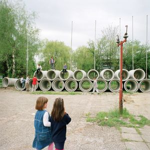 Children playing on pipes ready to be installed at Borovo Naselje. © Colin Dutton
