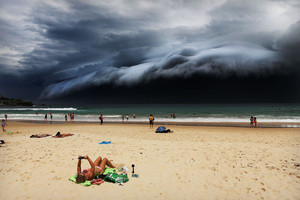 A massive 'cloud tsunami' looms over Sydney as a sunbather reads, oblivious to the approaching cloud on Bondi Beach, Sydney, Australia on 06 November 2015.