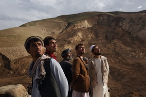 With the landslide in the background, men look to the sky as an Afghan National Army helicopter carrying Mohammad Karim Khalili, one of Afghanistan's two Vice Presidents flies over the disaster. Saturday 3 May, 2014.