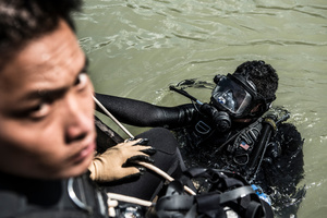 Divers Piseth Dara (L) and Lorn Sarath (R) on a mission in Kandal Province. Fishermen reported a large piece of UXO in the Mekong river and the team went to investigate.