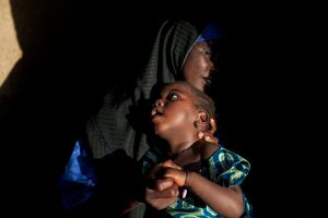 A young mother, Asnya Surajo, 25, is holding her daughter, Naimaatu Surajo, 4, a girl suffering from permanent brain damage and blindness. Asnya lost six children: two miscarriages and four while very young. Only her daughter Surajo was saved, but she survives as a continual victim of lead pollution. © Alex Masi