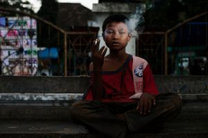 Cecep, who has lived on the streets for longer than he can remember after his mother passed away, poses for a photo as he smokes in Garut in West Java, Indonesia. © Michelle Siu