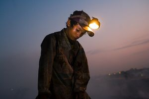 A young recycling worker, wearing a miner's lamp, just before dawn, on Smokey Mountain. © Nigel Dickinson.