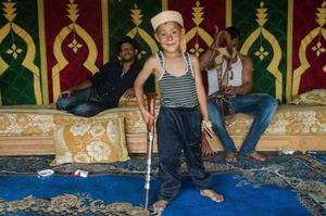 A young Moroccan boy poses with a child sized musket inside the traditional cherifian tent , during down time for the riding teams