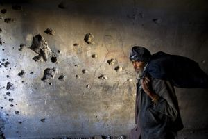 A man walks through one of the many bullet ridden hallways inside the abandoned Russian Cultural Center in Kabul. © Michael Christopher Brown