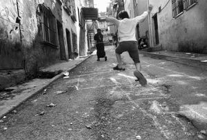 A boy plays hopscotch on a crumbling back street in Tarlabasi.