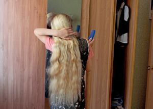 Eleven year old during hair braiding, right before church service in Petrovka, Omsk Oblast, Russia, 2014