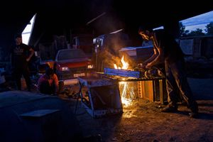 A man works at his metal salvage business in the Nova Gazela camp underneath the bridge. The enterprise employs dozens of people in the community. © Matt Lutton