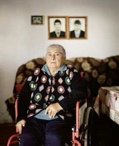 UNRECOGNIZED REPUBLIC OF NAGORNO-KARABAKH / Mardakert / 13.09.2011. Swetlana Karapitian in her house. The photos on the wall show her sons Armen (born 1974) and Kamo (born 1968) both of which joined a group of rebels in 1988 and have been reported as missing since 1992. Directly after Swetlana had been informed that her sons were missing, she could not walk any more.