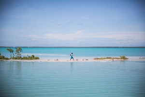 A boy walks from school to his house in Aberao village in South Tarawa, Kiribati. Kiribati is one of the countries most affected by sea level rise. During high tide many villages become inundated making large parts of the villages uninhabitable.