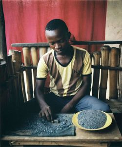 A boy works outside him home in the village of Tchonka, using a magnet to separate cassiterite bits from mined gravel.  Bags of cassiterite are then sold by the kilogram to middlemen.  The RM taxes households a portion of their profit or minerals in return for the security the RM provide. © Diana Zeyneb Alhindawi
