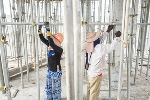 Keo Sokem 28 from Pursat Province and Khuon Tout 36 from Battambang Province work in unison to tighten scaffolding which is used to support the understide of a new level on a house construction.