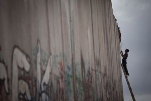 A Palestinian boy climb to the top of the Separation Wall near Qalandiya checkpoint, 2011.