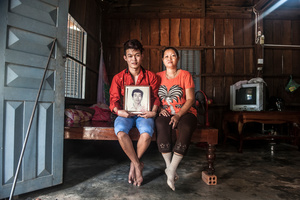 Kong (21) sits next to his mother Chiv Sokly (49) at their home in Kampong Speu Province, Cambodia.