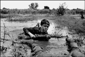 A thirteen year old Basij fighter advances on the southern front of Susangard Iraq-Iran war. Susangard, IRAN - March 1980 © Copyright 1979-2009 Alfred Yaghobzadeh. All rights reserved.
