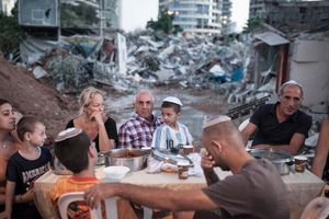 Families sit near an improvised dinner table near their demolished house in Givat Amal neighbourhood, Tel Aviv, Israel, 2014.