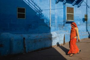 "A lady draped in the traditional ""sari"" covering her head with the ""pallu"" walking past the ubiquitous blue-walled house"