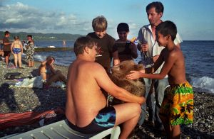 Georgia, Sukhumi, Abkhazia A tourist holds onto a bear which is being led by a hawker who offers tourists the opportunity to have their picture taken with the bear. Children pet the bear enthusiastically.© Petrut Calinescu