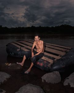 A man pose on a tube boat use to cross the natural border rio Suchiate between guatemala and mexico. Each years a estimated of 400 000 migrant cross.