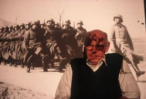 Willi Schneekloth at home in Schleswig-Holstein, Germany against a projected image of his army unit, 1999. Country: Germany, Born: 1921, Served: German Army, Conflict: World War II 1939-45. © Lori Grinker, courtesy of Nailya Alexander Gallery
