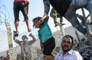 A refugee man holds a young girl as others climb over broken-down border fences to enter Turkish territory; Sanliurfa, Turkey, 14 June 2015.