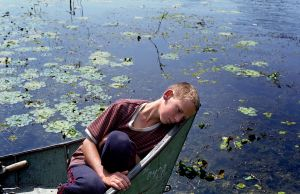 Romania, Tulcea, Danube Delta12-year-old Vanea rests in the prow of a fishing boat. He left school to work for a fisherman in the village of Sfistofca. The inhabitants of the Danube Delta live an isolated existance and make a living mainly by fishing and farming. The region's well-preserved delta eco-system was declared a UNESCO World Heritage Site in 1991.© Petrut Calinescu