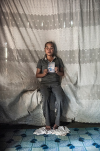 Phong Sopheak (33) holds a photograph of her husband Kun Sokhea who was 24 years old when a piece of UXO in the river exploded and killed him instantly.