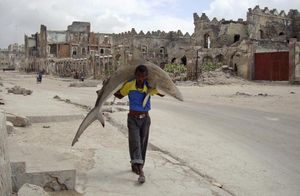 1st Prize Daily Life Single © Omar Feisal, Somalia, for Reuters. Man carries a shark through the streets of Mogadishu, Somalia, 23 September