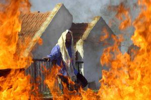 Homesh, Aug 05 - Behind a burning roadblock, a Jewish settler waits next to his home for Israeli soldiers to evacuate him © Natan Dvir