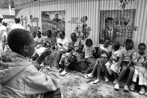 HIV AIDS KILLS: Orphan and abandoned children adopted by Charles and Esther Mulli knit happily outside a dorm room.                           © Lola Reid Allin