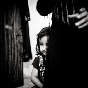 Syrian Refugee girl hiding behind her mother, Zarqa camp, Jordan