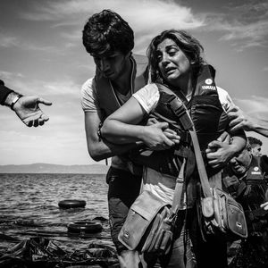 A woman is helped to the shore after a boat filled with refugees landed on the shore of Lesbos, Greece.