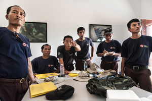 Members of the UXO salvage dive team take part in a mission brief in their dive shop in Kampong Chhanang, Cambodia.